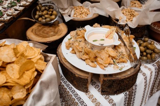 Lanches como batatas fritas, azeitonas e nozes estão na mesa da restauração