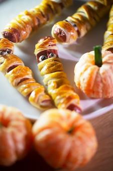 Lanches de halloween em forma de múmia feitos de massa e salsicha, bem como de tangerina
