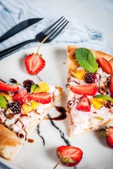 Lanches de verão. comida para festa. pizza de frutas com creme, groselha, iogurte, morangos, manga, pêssegos, bananas, amoras, chocolate, nozes, hortelã. na mesa azul claro. copyspace
