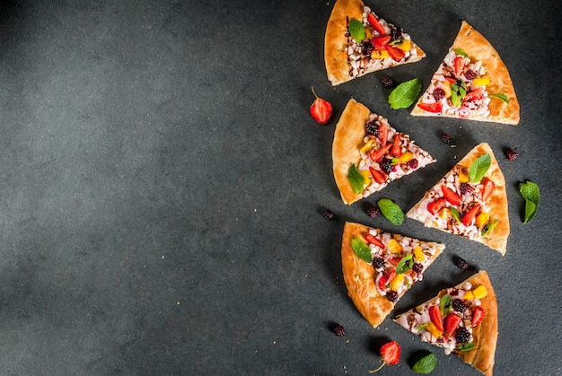 Lanches de verão. comida para festa. pizza de frutas com creme, groselha, iogurte, morangos, manga, pêssegos, bananas, amoras, chocolate, nozes, hortelã. na mesa preta. vista superior copyspace