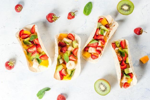 Lanches de verão. comida para uma festa. tacos de frutas com morangos, mangas, bananas, chocolate, menta