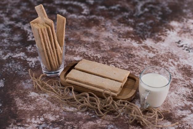 Lanches e biscoitos em travessa de madeira com um copo de leite, vista angular.