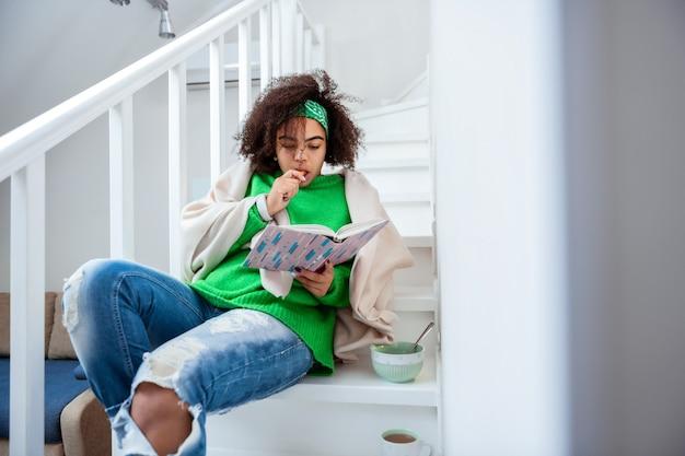 Lanches e laptop. garota tranquila e bonita, passando um tempo calmo nas escadas enquanto lê um livro interessante