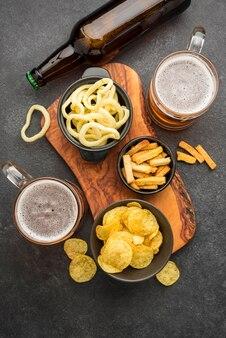 Lanches saborosos e canecas de cerveja na horizontal