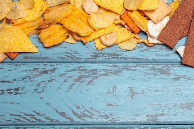 Lanches salgados. pretzels, batatas fritas, biscoitos. fundo de produtos não saudáveis