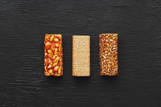 Lanches saudáveis. comida de dieta de aptidão. barra de grãos com amendoim, gergelim e sementes em uma placa de corte sobre uma mesa escura, barras de energia