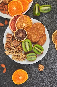 Lanches saudáveis - variedade de barra de granola de aveia, batatas fritas de arroz, amêndoa, kiwi, laranja seca