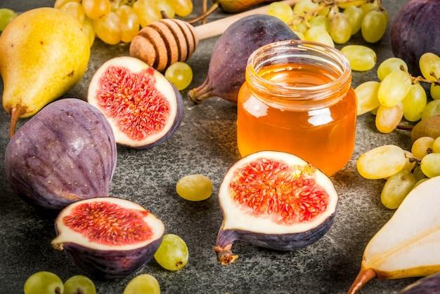 Lanches, sobremesas veganas dietéticas. frutos de outono (figos, peras, uvas) com mel