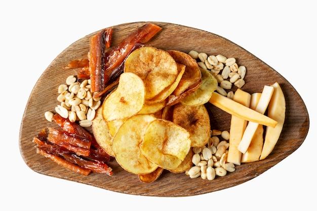 Lanches variados. batatas fritas, nozes, peixe seco e queijo defumado. apetitoso lanche de cerveja em uma placa de madeira. vista do topo. isolado sobre o branco