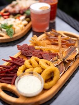 Lanches variados de cerveja fast food asas para churrasco anéis de cebola carnes de queijo curado com caneca de cerveja