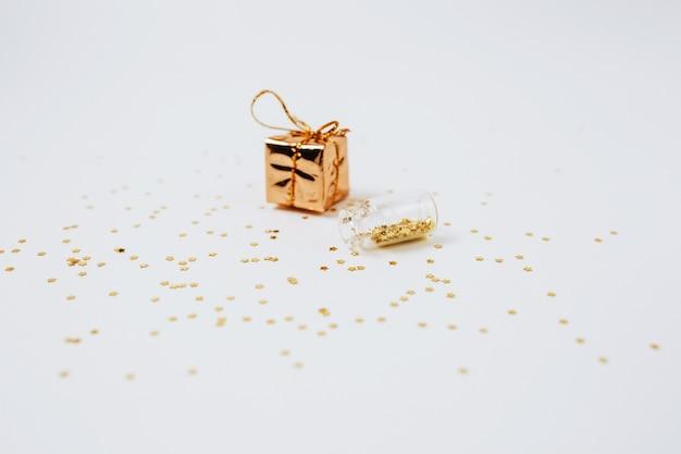 Lantejoulas de ouro e prata estão espalhadas em garrafas e um presente em um fundo branco
