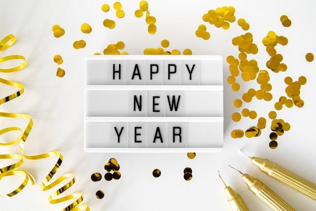 Lantejoulas douradas e fitas com citação de feliz ano novo