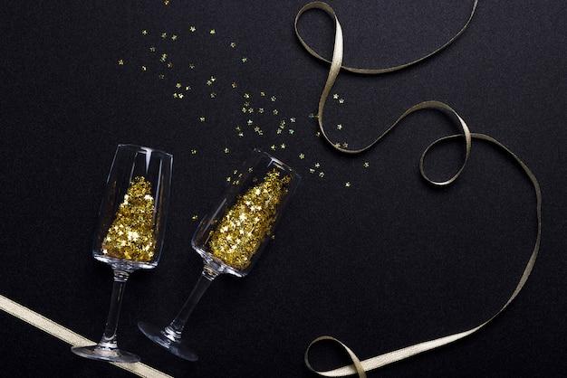 Lantejoulas em copos com fita na mesa