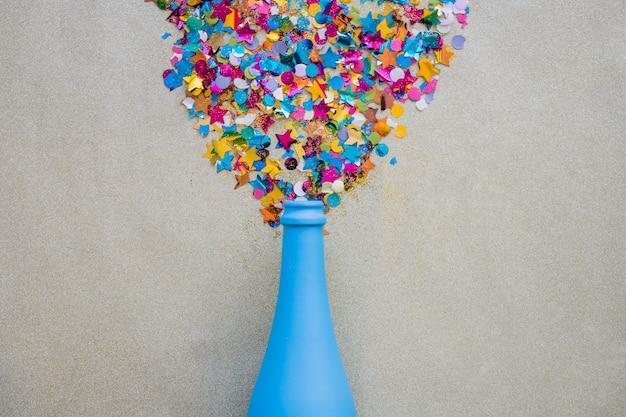Lantejoulas espalhadas de garrafa azul na mesa cinza