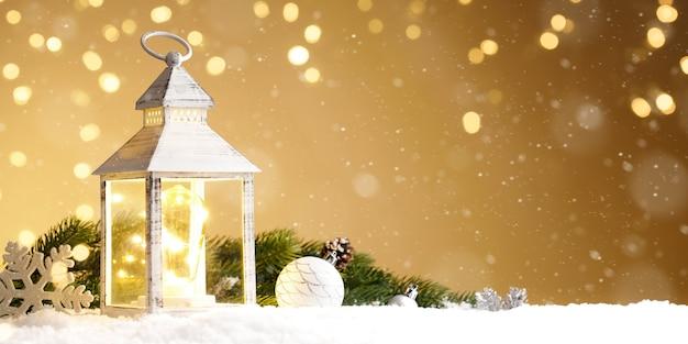 Lanterna acesa com decoração de natal na neve