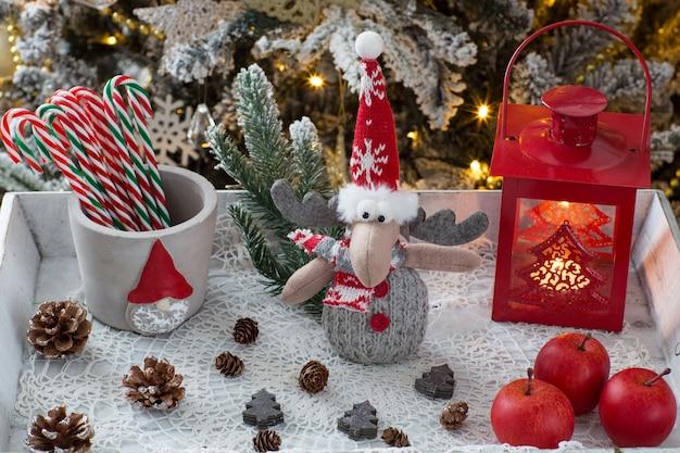 Lanterna, alce de brinquedo, cones e maçãs debaixo da árvore de natal
