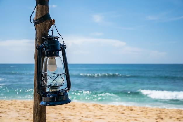 Lanterna azul em uma coluna com o mar e a praia no fundo em um dia ensolarado e claro