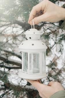 Lanterna branca na mão do homem contra o ramo coberto de neve.