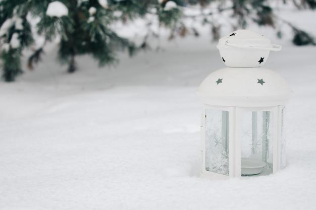 Lanterna branca na neve contra ramos cobertos de neve.