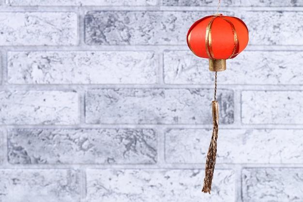 Lanterna chinesa diy feito a mão do ouro vermelho contra a parede de tijolo.