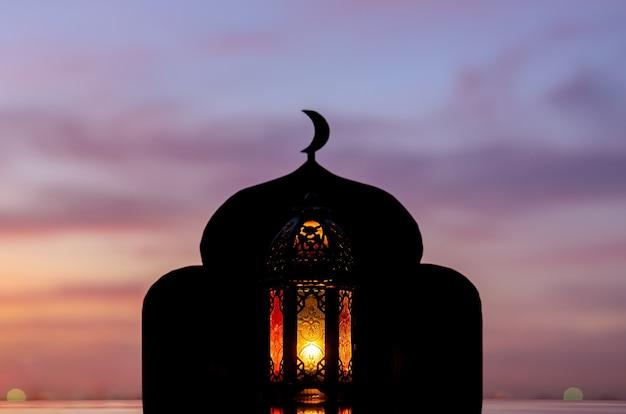 Lanterna com foco desfocado da mesquita que tem o símbolo da lua no topo e o céu do amanhecer.