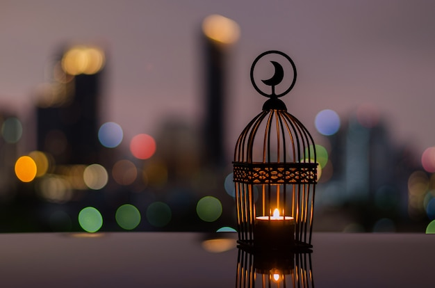 Lanterna com luz de fundo do céu ao anoitecer e bokeh da cidade para ramadan kareem.