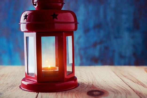 Lanterna com uma vela acesa dentro em uma mesa de madeira em um escuro