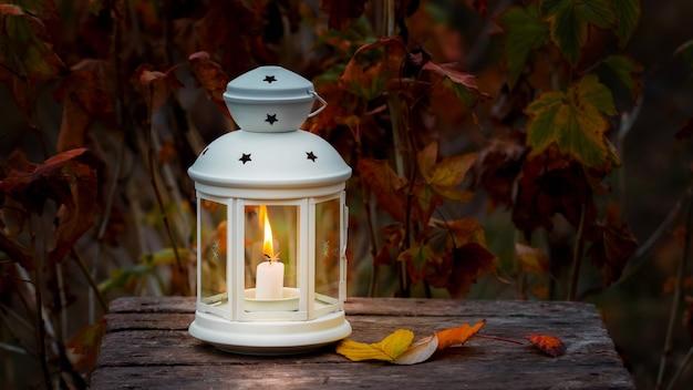 Lanterna com uma vela em um fundo de folhas de outono na noite escura.