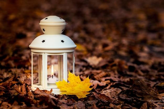 Lanterna com uma vela entre as folhas secas do outono à noite