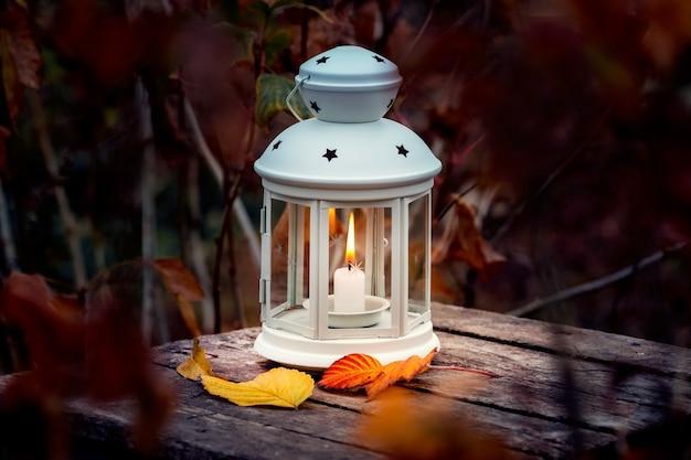 Lanterna com uma vela no jardim de outono à noite