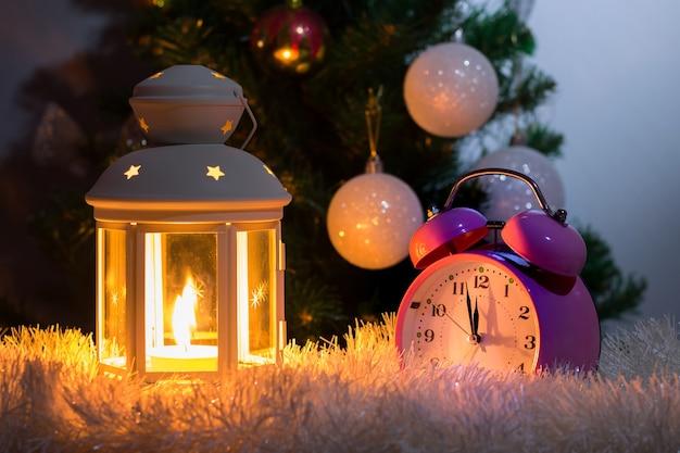 Lanterna com vela e relógio antes da árvore de natal à meia-noite_