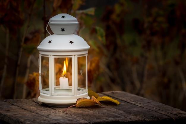 Lanterna com vela no jardim no fundo das folhas de outono à noite