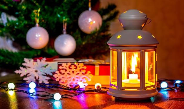 Lanterna com vela perto da árvore de natal e decorações de natal