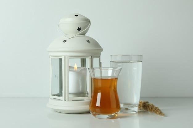 Lanterna, copos de chá e água na superfície branca