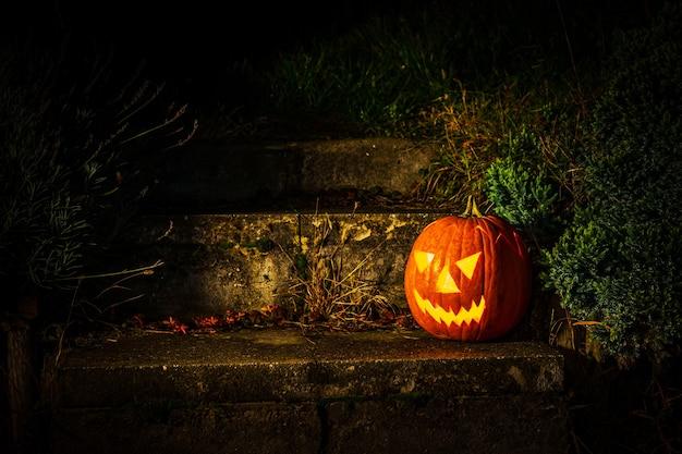 Lanterna de abóbora de halloween assustadora em escadas de concreto no jardim à noite