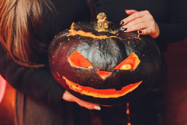 Lanterna de abóbora de halloween com folhas secas com fundo preto.