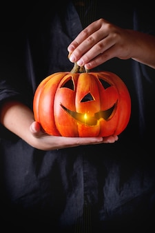 Lanterna de abóbora de halloween nas mãos da criança