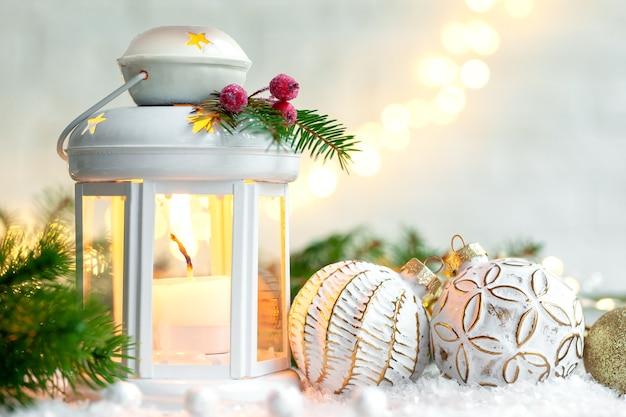 Lanterna de decoração de natal com velas acesas e bolas cristmas na luz de fundo festivo.