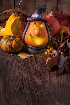Lanterna de halloween e abóboras em fundo de madeira