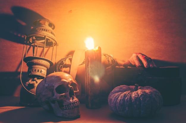 Lanterna de jack cabeça de abóbora de halloween e crânio humano em fundo de madeira