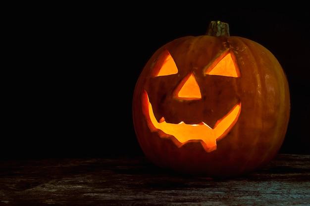 Lanterna de jack cabeça de abóbora de halloween em fundo de madeira