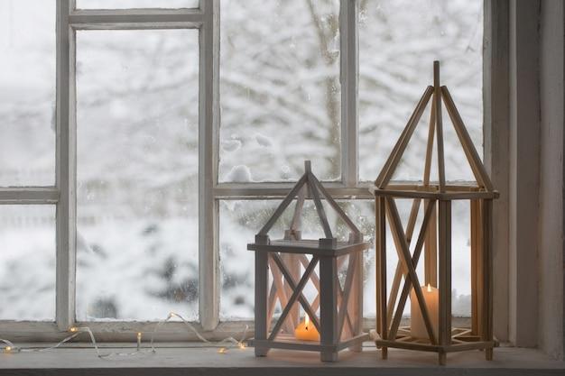 Lanterna de madeira no peitoril da janela na paisagem de inverno