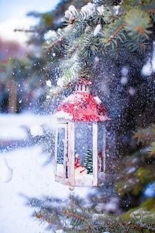Lanterna de natal com neve pendurado em um galho de abeto