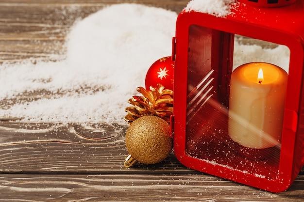 Lanterna de natal vermelho com vela acesa na mesa de madeira