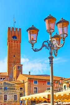 Lanterna de rua antiga e a torre cívica de treviso ao fundo, vêneto, itália