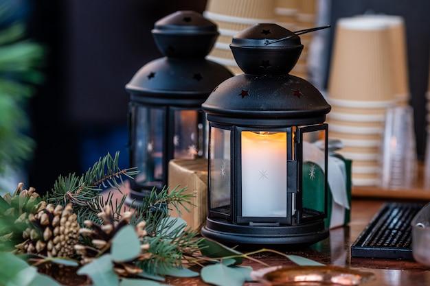 Lanterna de vela brilhante e decorações de natal em cima da mesa no mercado de natal em riga, letônia