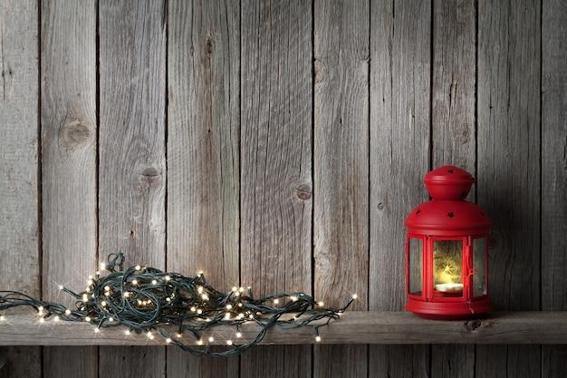 Lanterna de vela de natal e luzes em frente a parede de madeira com espaço de cópia