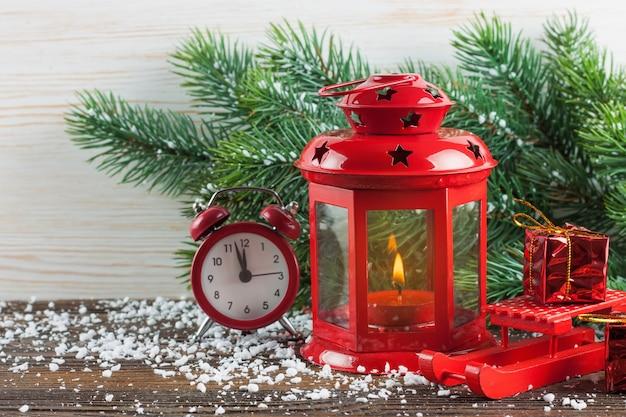Lanterna de vela vermelha de natal, árvore de natal e decorações em fundo branco de madeira.