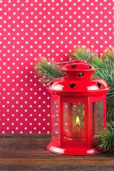 Lanterna de vela vermelha de natal e árvore de natal em fundo de bolinhas vermelhas.