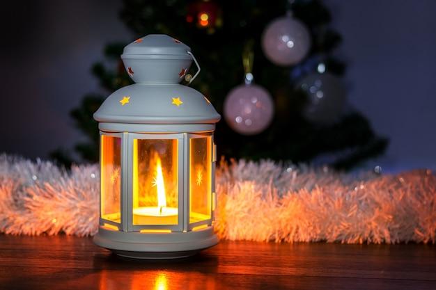 Lanterna decorativa com vela sob a árvore de natal à noite_